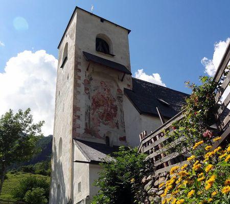 Das St. Nikolaus-Kirchlein mit seinem mächtigen Turm und dem St. Christophorus-Fresko an der Nordseite des Turms.